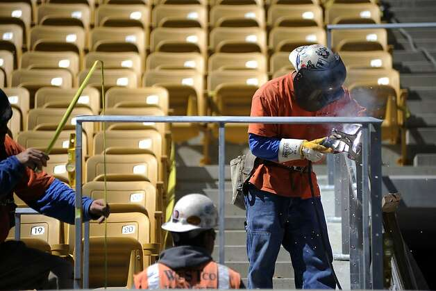 A group of construction workers weld a hand railing near the bottom of the stadium seating.  Assistant AD / Capital Planning & Management Bob Milano Jr. gave a tour of the soon to be completed renovations of Cal Memorial Stadium Tuesday July 31st, 2012 Photo: Michael Short, Special To The Chronicle