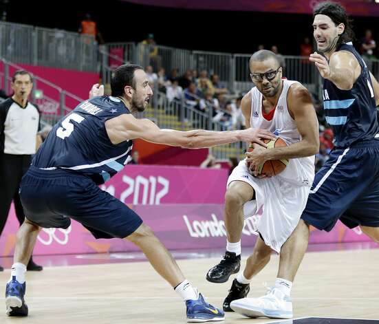 France's Tony Parker, center, drives between Argentina's Manu Ginobili (5) and Argentina's Luis Scola, right, during the second half of a preliminary men's basketball game at the 2012 Summer Olympics, Tuesday, July 31, 2012, in London. (Eric Gay / Associated Press)