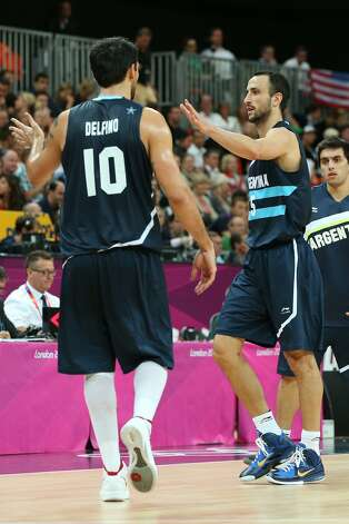 Manu Ginobili #5 of Argentina celebrates with team mate Carlos Delfino  on the way to a time out in the Men's Basketball Preliminary Round match between France and Argentina on Day 4 of the London 2012 Olympic Games at Basketball Arena on July 31, 2012 in London, England. (Christian Petersen / Getty Images)