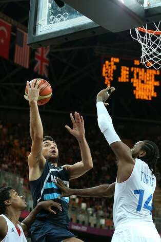Carlos Delfino #10 of Argentina shoots over Ronny Turiaf #14 of France  in the Men's Basketball Preliminary Round match between France and Argentina on Day 4 of the London 2012 Olympic Games at Basketball Arena on July 31, 2012 in London, England. (Christian Petersen / Getty Images)