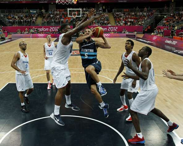 Argentina's Manu Ginobili, center, drives between France's players during their men's preliminary round group A basketball match at the 2012 Summer Olympics on Tuesday, July 31, 2012, in London. (Mike Segar / Associated Press)