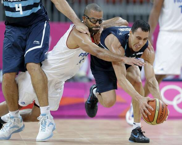 France's Tony Parker, center, dives to stop Argentina's Pablo Prigioni, right, during the second half of a preliminary men's basketball game at the 2012 Summer Olympics, Tuesday, July 31, 2012, in London. Argentina's Luis Scola is at left. (Eric Gay / Associated Press)