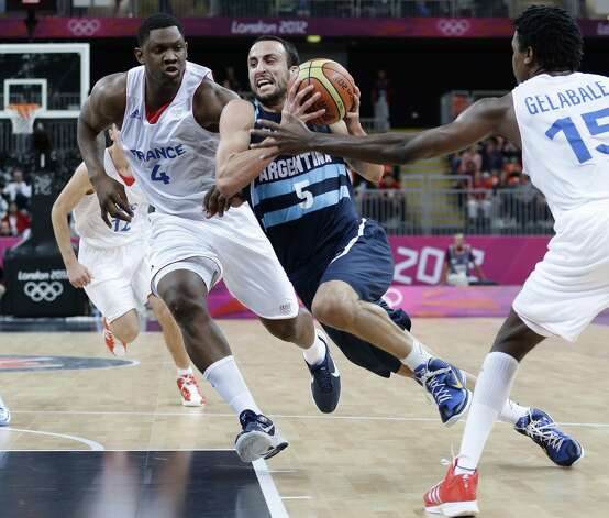 Argentina's Manu Ginobili (5) drives to the basket between France defenders Kevin Seraphin (4) and Mickael Gelabale during the first half of a preliminary men's basketball game at the 2012 Summer Olympics, Tuesday, July 31, 2012, in London. (Eric Gay / Associated Press)