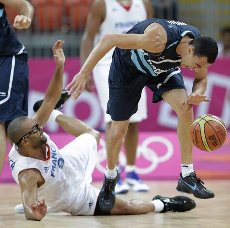 France's Tony Parker, left, falls as he tries to stop Argentina's Pablo Prigioni, right, during the second half of a preliminary men's basketball game at the 2012 Summer Olympics, Tuesday, July 31, 2012, in London. Argentina's Luis Scola is at left. (Eric Gay / Associated Press)