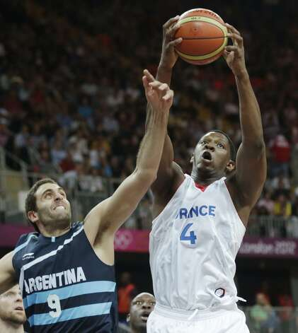 France's Kevin Seraphin, right, pulls down a rebound against Argentina's Juan Gutierrez during a men's basketball game at the 2012 Summer Olympics, Tuesday, July 31, 2012, in London. (Charles Krupa / Associated Press)