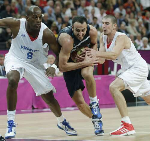 Argentina's Manu Ginobili, center, threads between France's Ali Traore, left, and Nando de Colo on a drive to the basket during a men's basketball game at the 2012 Summer Olympics, Tuesday, July 31, 2012, in London. (Charles Krupa / Associated Press)
