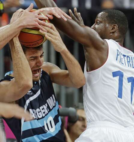 Argentina's Carlos Delfino, left, is trapped by France's Florent Pietrus during a men's basketball game at the 2012 Summer Olympics, Tuesday, July 31, 2012, in London. (Charles Krupa / Associated Press)