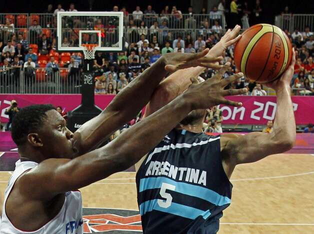 France's Kevin Seraphin, left, tries to block the shot of Argentina's Manu Ginobili during their men's preliminary round group A basketball match at the 2012 Summer Olympics on Tuesday, July 31, 2012, in London. (Mike Segar / Associated Press)