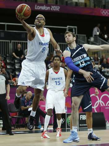 France's Tony Parker drives past Argentina's Andres Nocioni during a men's basketball game at the 2012 Summer Olympics, Tuesday, July 31, 2012, in London. (Charles Krupa / Associated Press)