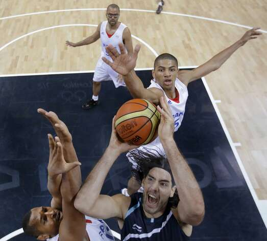 Argentina's Luis Scola, right, drives to the basket past France's Nicolas Batum (5) and Boris Diaw, left, during a men's basketball game at the 2012 Summer Olympics, Tuesday, July 31, 2012, in London. At rear is France's Tony Parker. (Charles Krupa / Associated Press)