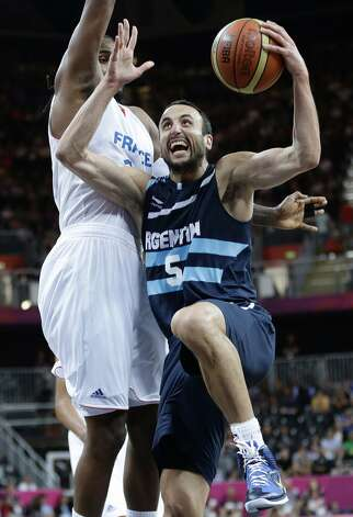 Argentina's Manu Ginobili (5) drives to the basket against France's Ronny Turiaf, left, during the first half of a preliminary men's basketball game at the 2012 Summer Olympics, Tuesday, July 31, 2012, in London. (Eric Gay / Associated Press)