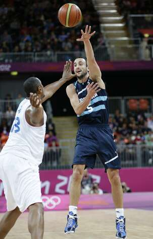 Argentina's Manu Ginobili, right, passes the ball past France's Boris Diaw,  left, during the first half of a preliminary men's basketball game at the 2012 Summer Olympics, Tuesday, July 31, 2012, in London. (Eric Gay / Associated Press)