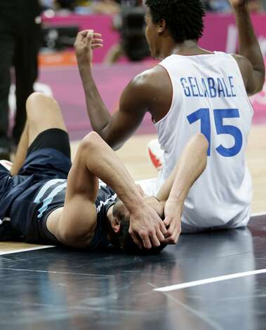 Argentina's Manu Ginobili, left, reacts after he was called for a foul against France's Mickael Gelabale (15) during the second half of a preliminary men's basketball game at the 2012 Summer Olympics, Tuesday, July 31, 2012, in London. (Eric Gay / Associated Press)
