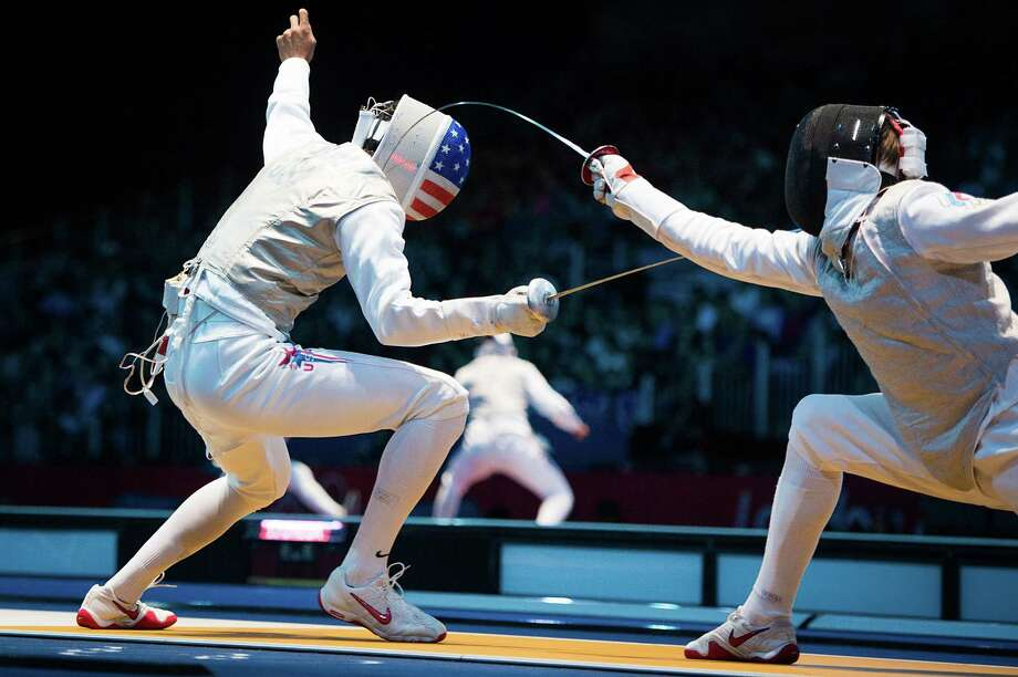Alexander Massialas of the U.S. (left) competes against Alexey Cheremisinov of Russia during men's individual foil fencing. Photo: Smiley N. Pool, Houston Chronicle / © 2012  Houston Chronicle