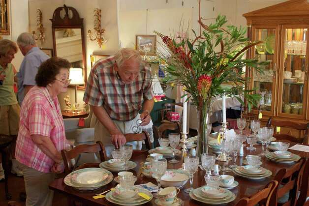 Shoppers look over glassware at the Keeler Tavern Museum's Annual Antiques and Treasures Sale last summer in Ridgefield. This year's sale is Aug. 3 to 5. Photo: Contributed Photo/Elise Haas