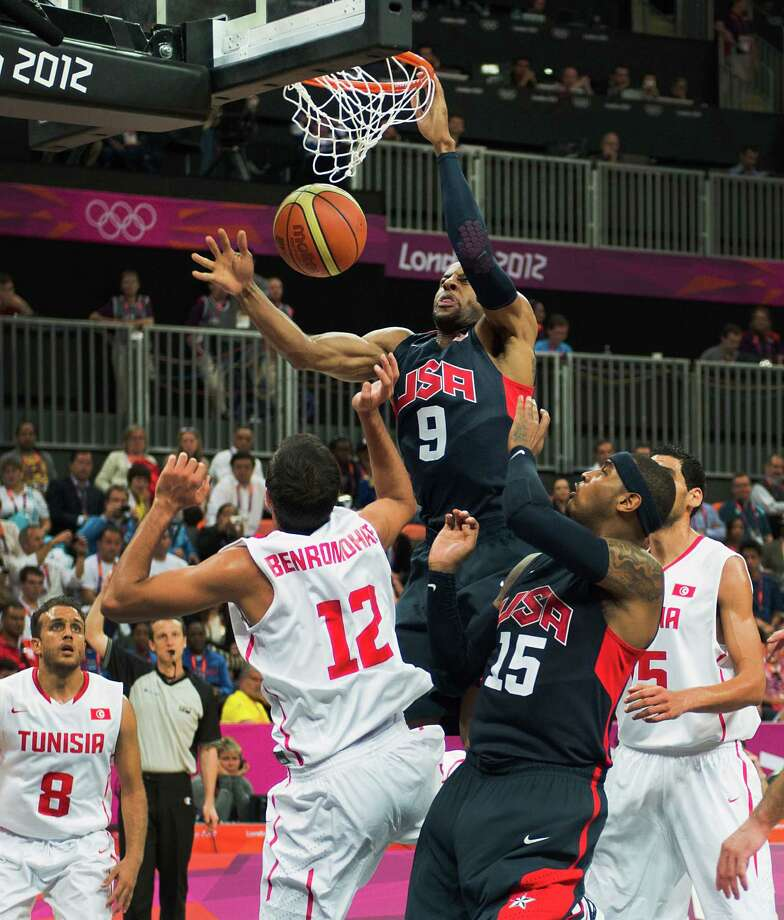 USA's Andre Iguodala dunks the ball over Tunisia's Makram Ben Romdhane during a men's preliminary round basketball game at the 2012 London Olympics on Tuesday, July 31, 2012. Photo: Smiley N. Pool, Houston Chronicle / © 2012  Houston Chronicle