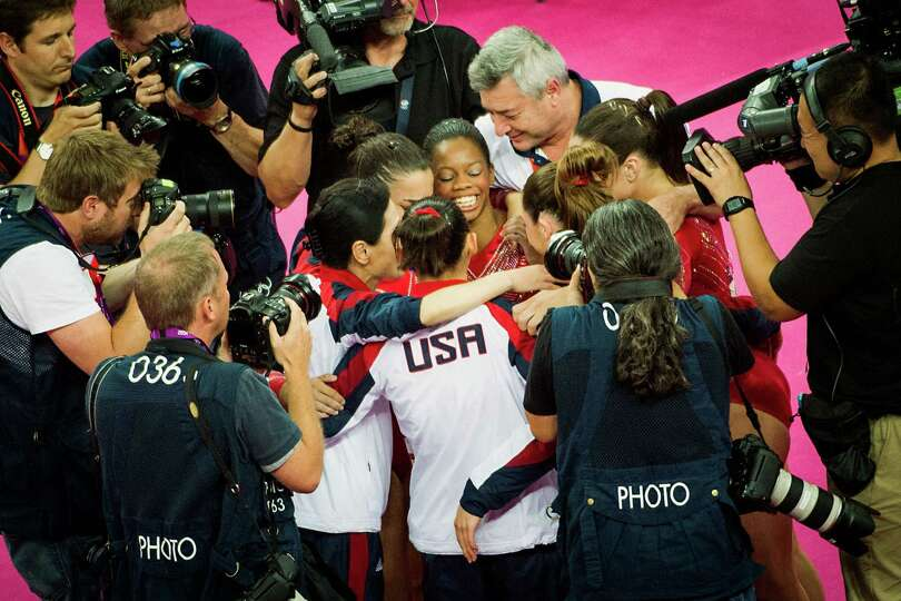 Gabby Douglas, facing, celebrates with teammates as photographers crowd around the U.S. the after th