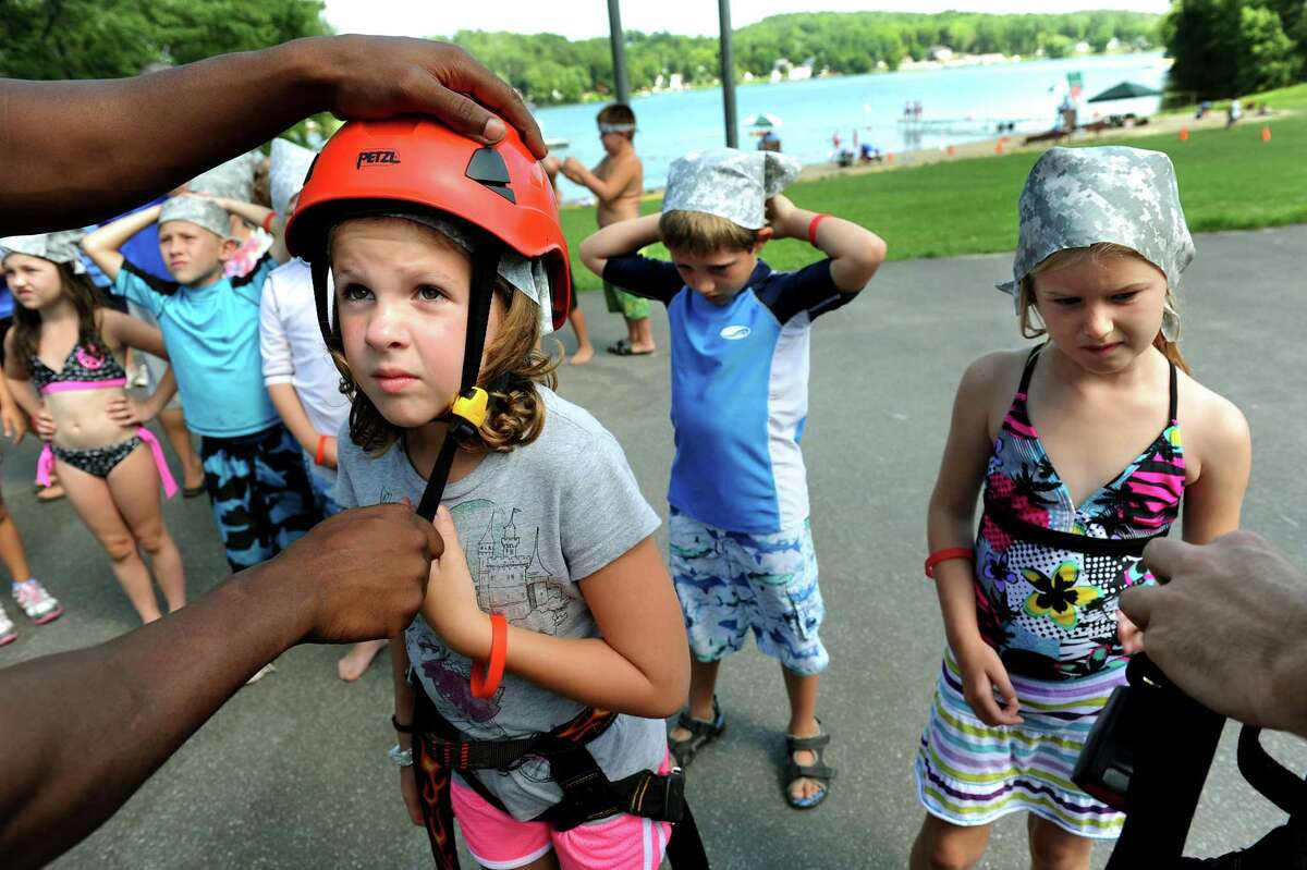 Olivia Urquhart, 7, of Troy, left, gets suited up to climb a portable rock wall on Tuesday, July 31, 2012, at Snyders Lake Day Camp in Wynantskill, N.Y. Army and Air Force members of the New York State Counter Drug Task Force provided a brief drug education class and the climbing wall for children attending camp. (Cindy Schultz / Times Union)