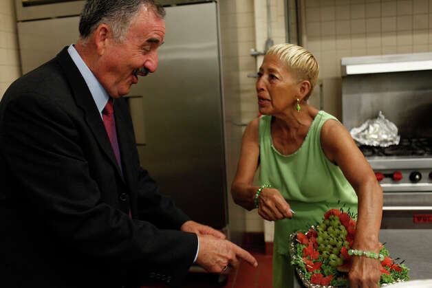 Ciro Rodriguez laughs as he realizes kitchen volunteers Mickie Olivio, right, and Dora Galvan, not pictured, spelled his name out in grapes on a piece of watermelon at the Harlandale Civic Center where his supporters gathered to watch the results come in from his runoff against Pete Gallego for the Democratic nomination for U.S. House District 23 in San Antonio on Tuesday, July 31, 2012. Photo: Lisa Krantz, San Antonio Express-News / San Antonio Express-News