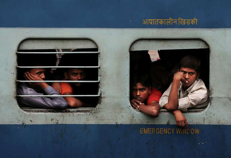 Indian stranded passengers wait inside a stalled train as they wait for the services to resume after a power outage in New Delhi, India, Tuesday, July 31, 2012. India's energy crisis cascaded over half the country Tuesday when three of its regional grids collapsed, leaving 620 million people without government-supplied electricity for several hours in, by far, the world's biggest blackout. Hundreds of trains stalled across the country and traffic lights went out, causing widespread traffic jams in New Delhi. (AP Photo/Kevin Frayer) Photo: Kevin Frayer