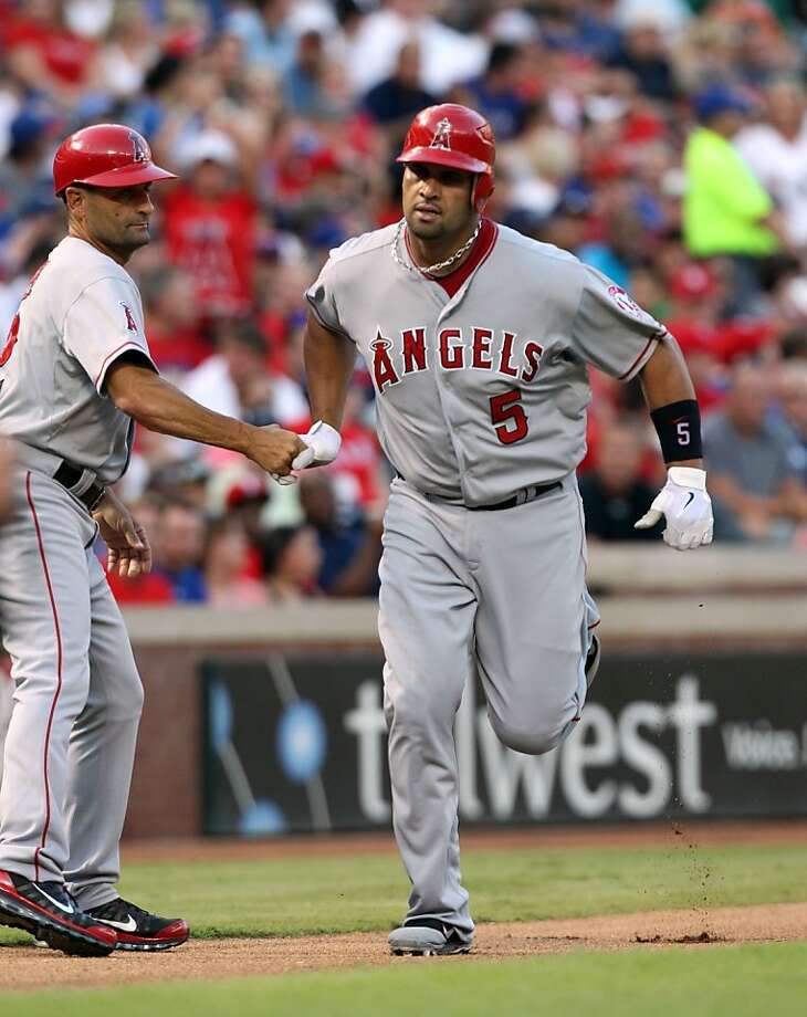 ARLINGTON, TX - JULY 31: Albert Pujols #5 of the Los Angeles Angels of Anaheim is congratulated by 3rd base coach Dino Ebel after hitting a two-run homerun, his second homer of the game against the Texas Rangers in the top of  the 6th inning on July 31, 2012 at the Rangers Ballpark in Arlington in Arlington, Texas. (Photo by Layne Murdoch/Getty Images) Photo: Layne Murdoch, Getty Images