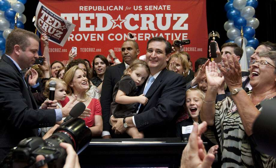 The crowd cheers on Ted Cruz as he holds his daughter Caroline after his victory. Among his supporters on stage at the JW Marriott in the Galleria is his wife, Heidi, shown with their daughter Catherine.