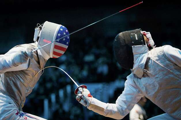 Alexander Massialas of the USA, left, competes against Alexey Cheremisinov of Russia during men's individual foil fencing at the 2012 London Olympics on Tuesday, July 31, 2012. Photo: Smiley N. Pool, Houston Chronicle / © 2012  Houston Chronicle