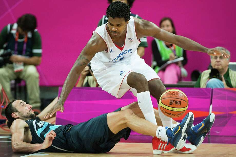 Argentina's Manu Ginobili hits the floor in a collision with France's Mickael Gelabale during a men's preliminary round basketball game at the 2012 London Olympics on Tuesday, July 31, 2012. Photo: Smiley N. Pool, Houston Chronicle / © 2012  Houston Chronicle