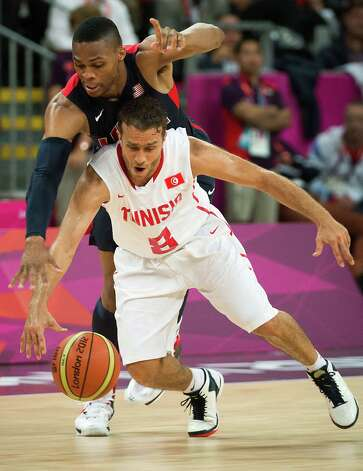 USA's Russell Westbrook reaches over Tunisia's Marouan Kechrid to try and make a steal during a men's preliminary round basketball game at the 2012 London Olympics on Tuesday, July 31, 2012. Photo: Smiley N. Pool, Houston Chronicle / © 2012  Houston Chronicle
