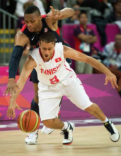 USA's Russell Westbrook reaches over Tunisia's Marouan Kechrid to try and make a steal during a men'