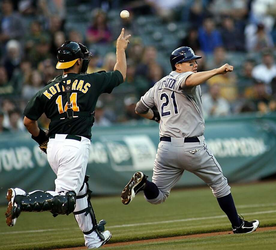 Tampa Bay Rays Jose Lobato is caught in a rundown by Oakland Athletics catcher George Kottaras in the third inning of a baseball game in Oakland, Calif., Tuesday, July 31, 2012. He was tagged out by pitcher Tommy Milone.  (AP Photo/Dino Vournas) Photo: Dino Vournas, Associated Press
