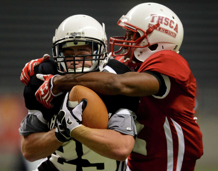 Midway's Justin Richter (left) is tackled by Tenaha's Reginald Davis (right) after Richter intercepted a pass during the 2012 Texas high school coaches association all-star football game on July 31, 2012 at the Alamodome. Photo: JOHN ALBRIGHT, John Albright, For The Express-News / San Antonio Express-News