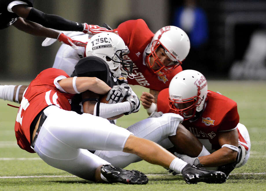 Smithson Valley's Ryan Griffith (left), Steele's Evan Lyons (top) and Laredo United's Michael Byrd (right) tackle Clarksville's H.B. Rosser (black Jersey)  during the 2012 Texas high school coaches association all-star football game on July 31, 2012 at the Alamodome. Photo: JOHN ALBRIGHT, John Albright, For The Express-News / San Antonio Express-News