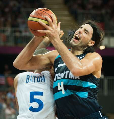 Argentina's Luis Scola collides with France's Nicolas Batum as he drives to the basket during  a men's preliminary round basketball game at the 2012 London Olympics on Tuesday, July 31, 2012. (Smiley N. Pool / Houston Chronicle)