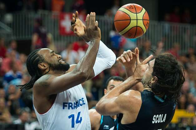 France's Ronny Turiaf and Argentina's Luis Scola fight for a rebound during a men's preliminary round basketball game at the 2012 London Olympics on Tuesday, July 31, 2012. (Smiley N. Pool / Houston Chronicle)
