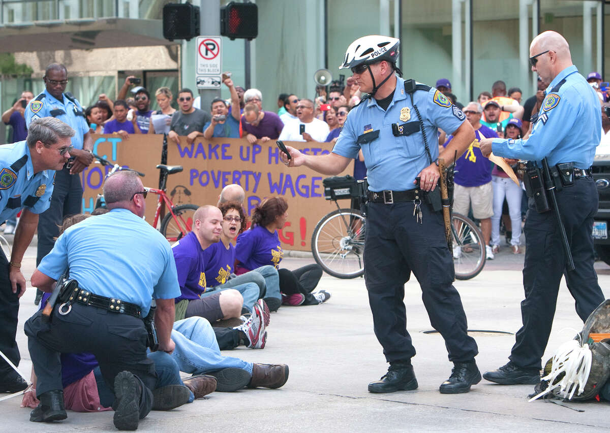 Protesters sit in the intersection of Dallas and Smith Streets in protest of janitors' current wages Wednesday, August 1, 2012, in Houston. Civil rights and labor activists are currently demonstrating civil disobedience and supporting janitors who are entering their fourth week of an unfair labor practices strike.