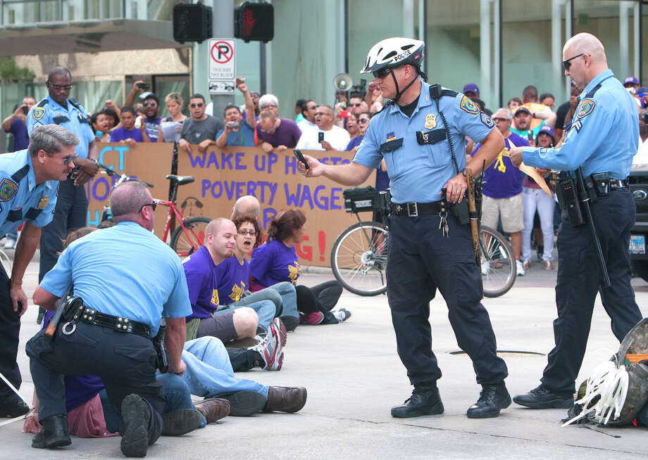 Protesters sit in the intersection of Dallas and Smith Streets in protest of janitors' current wages Wednesday, August 1, 2012, in Houston. Civil rights and labor activists are currently demonstrating civil disobedience and supporting janitors who are entering their fourth week of an unfair labor practices strike. Photo: Cody Duty, Houston Chronicle / © 2011 Houston Chronicle