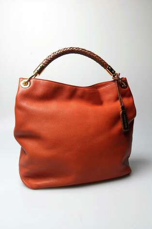 Michael Kors tangerine shoulder bag $895, from SAKS Fifth Avenue Friday, June 8, 2012. Part of the women's handbags that will transition from mid-summer into fall. Photo: Julysa Sosa, Staff / © 2012 San Antonio Express-News