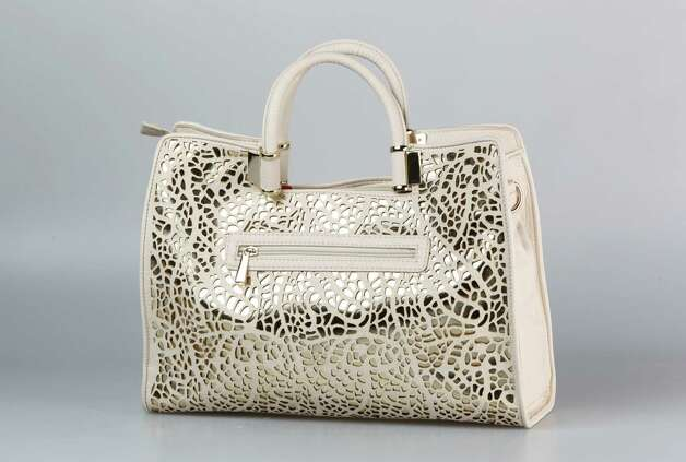 Iranka Trump off white and gold metallic laser cut leather handbag $175 from Dillards at Northstar Mall Friday, June 8, 2012. Part of the women's handbags that will transition from mid-summer into fall. Photo: Julysa Sosa, Staff / © 2012 San Antonio Express-News