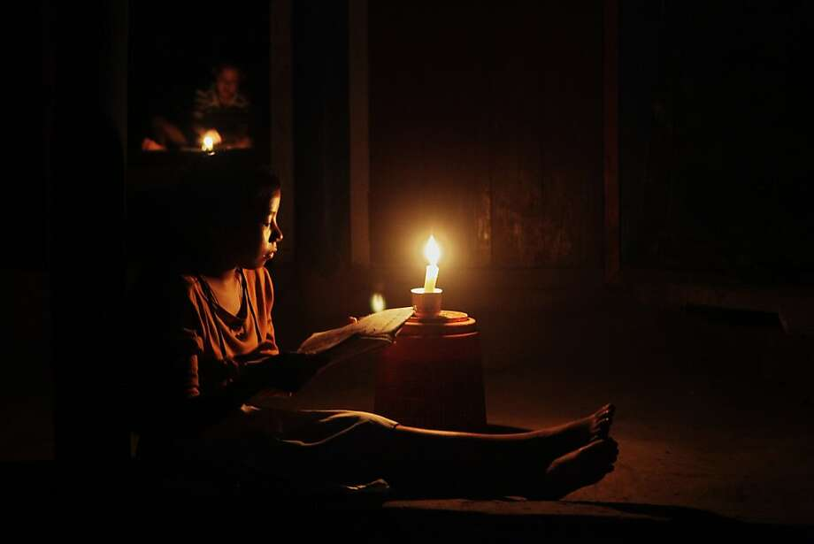 A young Indian girl reads a book by candle light during a regular load shedding in Mainakhurung on the outskirts of Gauhati, India, Wednesday, Aug. 1, 2012. Factories and workshops across India were up and running again Wednesday, a day after a major system collapse led to a second day of power outages and the worst blackout in history leaving an estimated 620 million people without electricity. (AP Photo/Anupam Nath) Photo: Anupam Nath, Associated Press