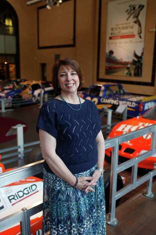 Susan Carbonaro, director of the Saratoga Automobile Museum in Saratoga Springs, N.Y.,  Monday July 16, 2012, stands for a picture in front of the current exhibit ?Moonshine to Millionaires:  NASCAR History, Heroes and Technology? which runs through Nov. 25. (Dan Little/Special to the Times Union) Photo: Dan Little / Copyright: All Rights Reserved Brett Carlsen