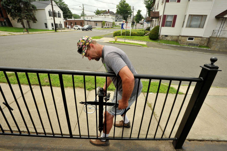 Clay Pierce, owner of the property at the corner of West and Montgomery streets in Danbury, installs a ghost bike memorial in honor of 7-year-old Alberto Perez on Wednesday, August 1, 2012. Perez died after he was struck by a minivan while riding his bike near the intersection on June 19, 2011. Photo: Jason Rearick / The News-Times