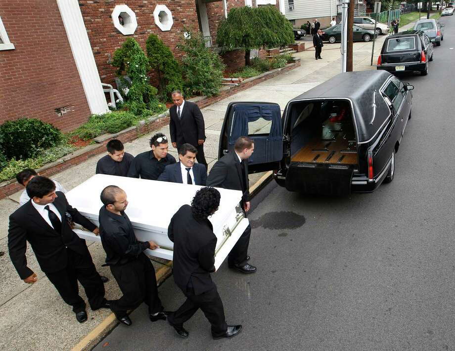 Pallbearers carry a casket to one of three hearses sit in front of the Madison Avenue Baptist Church in Paterson, N.J, Wednesday, Aug. 1, 2012, after funeral services for a Peruvian brother and sister and their grandmother. Photo: Mel Evans, Associated Press / AP