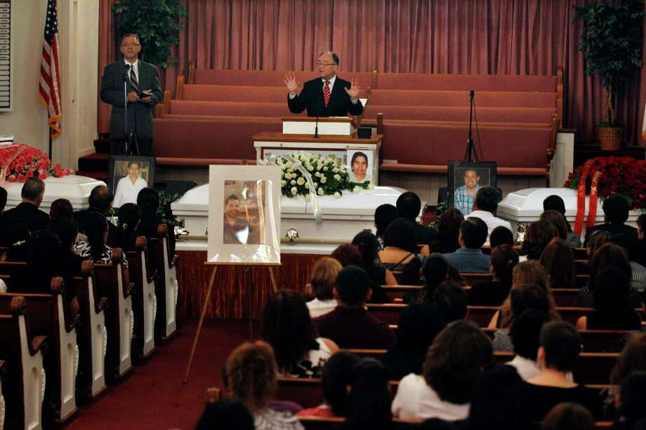 As pastor Jay Harvey delivers a sermon, three caskets are seen in the front of the Madison Avenue Baptist Church in Paterson, N.J. on Wednesday, Aug. 1, 2012 during funeral services for a Peruvian brother and sister and their grandmother. Photo: Mel Evans, Associated Press / AP