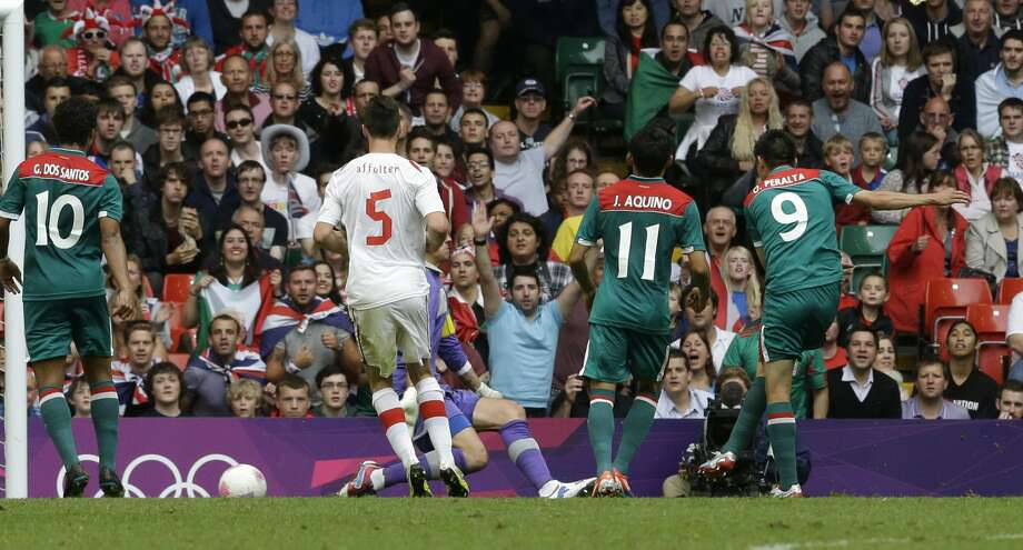 Mexico's Oribe Peralta, right, scores during the men's group B soccer match between Mexico and Switzerland, at the Millennium Stadium in Cardiff, Wales, at the 2012 London Summer Olympics, Wednesday, Aug. 1, 2012. (Luca Bruno / Associated Press)