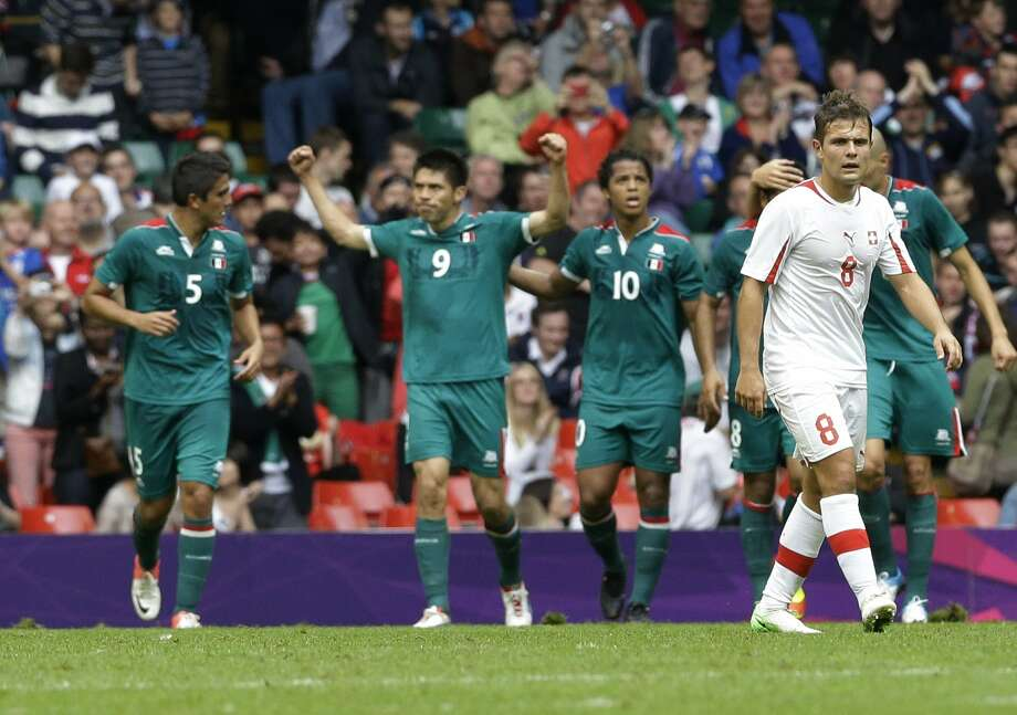 Switzerland's Amir Abrashi walks away as Mexico's Oribe Peralta celebrates after scoring during the men's group B soccer match between Mexico and Switzerland, at the Millennium stadium in Cardiff, Wales, at the 2012 London Summer Olympics, Wednesday, Aug. 1, 2012. (Luca Bruno / Associated Press)