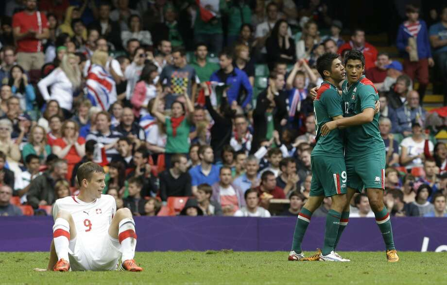 Switzerland's Fabian Frei, left, reacts as Mexico's Oribe Peralta, second from right, and his teammate Mexico's Raul Jimenez celebrate at the end of their men's group B soccer match at the Millennium stadium in Cardiff, Wales, at the 2012 London Summer Olympics, Wednesday, Aug. 1, 2012. Mexico won 1-0 and advances to the quarterfinals. (Luca Bruno / Associated Press)