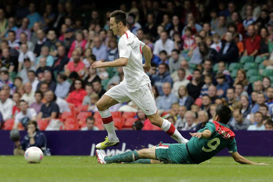 Switzerland's Francois Affolter, left, is tackled by Mexico's Oribe Peralta during their men's group B soccer match at the Millennium stadium in Cardiff, Wales, at the 2012 London Summer Olympics, Wednesday, Aug. 1, 2012. (Luca Bruno / Associated Press)
