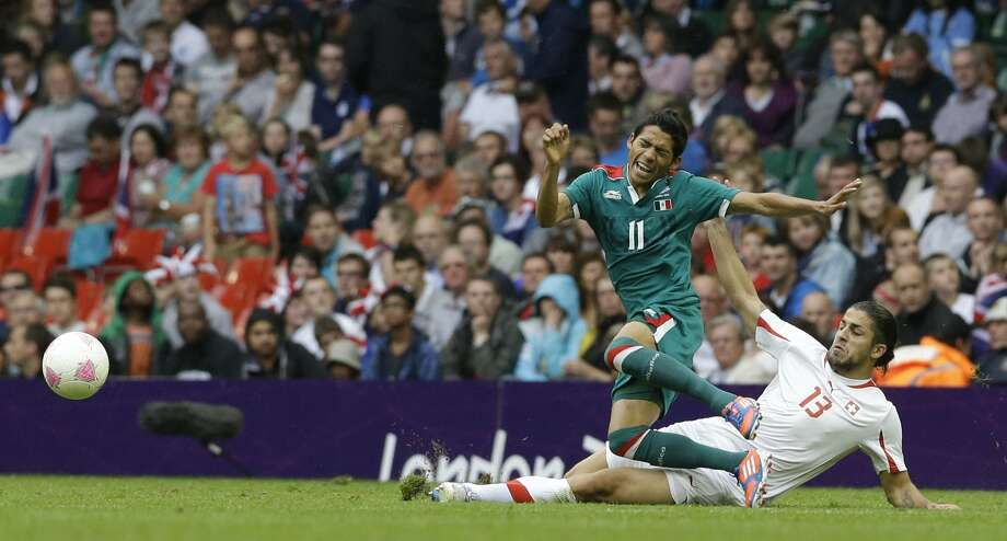 Mexico's Javier Aquino, left, is tackled by Switzerland's Ricardo Rodriguez during the men's group B soccer match between Mexico and Switzerland, at the Millennium stadium in Cardiff, Wales, at the 2012 London Summer Olympics, Wednesday, Aug. 1, 2012. (Luca Bruno / Associated Press)