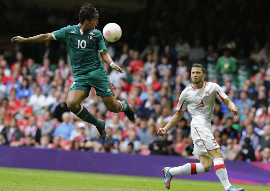 Mexico's Giovani Dos Santos, left, jumps for the ball as Switzerland's Fabio Daprela looks on during the men's group B soccer match between Mexico and Switzerland, at the Millennium stadium in Cardiff, Wales, at the 2012 London Summer Olympics, Wednesday, Aug. 1, 2012. (Luca Bruno / Associated Press)
